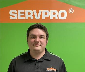 picture of man smiling in front of green SERVPRO wall