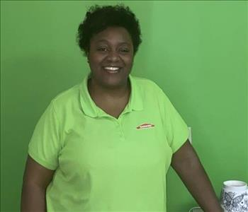 picture of woman smiling in front of green SERVPRO wall