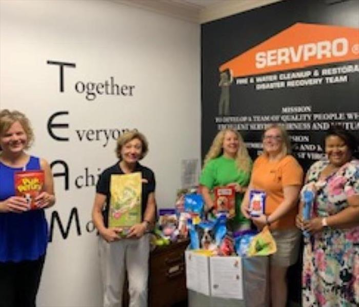 5 women standing up holding pet food and supplies in front of a wall that says SERVPRO
